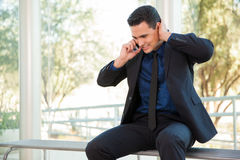 Hearing bad news on the phone. Young man on a suit stressing out from bad news he just heard over the phone Stock Photos