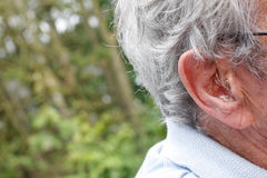 Hearing device. An older man with a hearing device Royalty Free Stock Photos