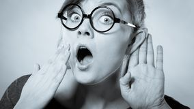 Shocked girl eavesdropping. Hearing gesture shock emotion concept. Shocked girl eavesdropping. Young nerdy stunned lady in glasses listening expressing disbelief stock photo