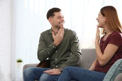 Hearing impaired friends using sign language for communication on sofa. In living room stock photography