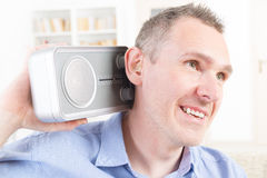 Hearing impaired man trying to listen radio Stock Photo