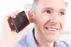 Hearing impaired man using mobile phone Stock Image