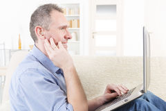Hearing impaired man working with laptop Stock Photo