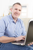 Hearing impaired man working with laptop Royalty Free Stock Photography