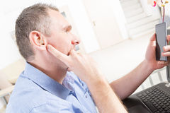 Hearing impaired man working with laptop and mobile phone Royalty Free Stock Photo