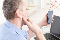 Hearing impaired man working with laptop and mobile phone. At home or office Stock Image