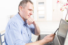 Hearing impaired man working with laptop and mobile phone Royalty Free Stock Images