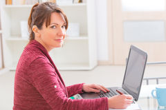 Hearing impaired woman working with laptop Stock Image
