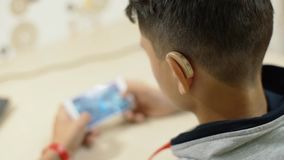 A hearing-impaired young man in a hearing aid plays on a smartphone. stock footage