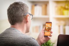 Ordering food online by smartphone. Hearing impairment man ordering food online by smart phone. Concept of ordering food in office, workplace or home stock photography