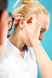 Hearing loss. The doctor assumes the women hearing aid in your ear royalty free stock images