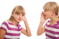 Hearing problems. Girl shouting to another girl who can't hear well. Isolated on white stock image