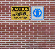 Hearing Protection Required. Safety signs on hearing protection mounted on a brick wall royalty free stock images