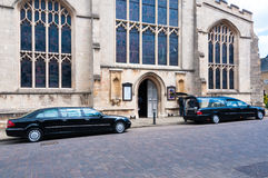 Hearse carrying a coffin parked outside church Royalty Free Stock Photography