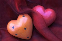 From the heart... Stone-hearts in pink and orange lying on red tulle Stock Photo