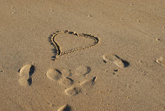 Heart. Drawed by hand on sand with footsteps near it royalty free stock photography