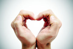 Heart. Man hands forming a heart on a vignetted background stock photography