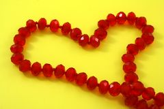 Heart. Of the red beads on a yellow background Royalty Free Stock Photos