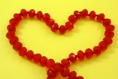 Heart. Of the red beads on a yellow background Stock Image