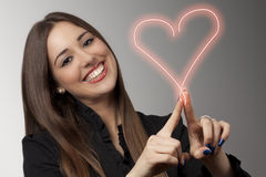 Heart. Beautiful young woman is drawing heart Stock Images