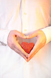 Heart. Bright red heart in the man's hands Royalty Free Stock Images