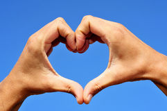 Heart. Man hands forming a heart over the blue sky stock images