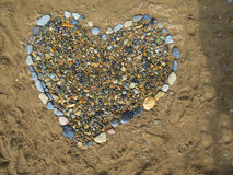 Heart. Pattern in the form of a heart made of many small stones on the sand Stock Image