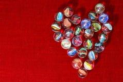Heart. Of glass marbles on red velvet Stock Image