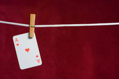 Heart ace. With clothes peg  rope on red background Royalty Free Stock Photos