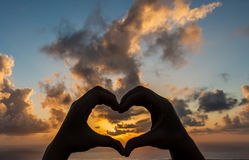 Heart against beautiful sunset. Heart symbol has been created  with help of hands. Heart symbol against beautiful sunset background Royalty Free Stock Photos