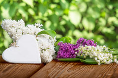 Heart against lily of the valley and lilac Royalty Free Stock Images