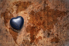 Heart with alaska state flag  on a vintage world map crack paper background. Concept Stock Photography
