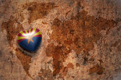 Heart with arizona state flag on a vintage world map crack paper background. Concept stock photography