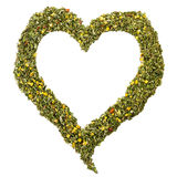 Heart arranged with herbal tea leaves. Heart shape carefully arranged with herbal tea leaves by hand, symbolizing health and love Royalty Free Stock Photography