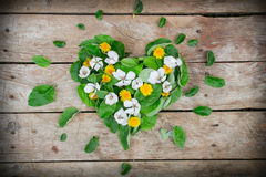 Heart arrangement made of leaves and flowers rustic table Royalty Free Stock Image