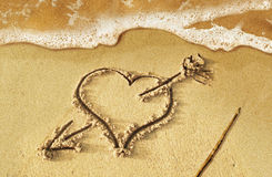 Heart with arrow, as love sign, drawn on the beach shore, with s Stock Image