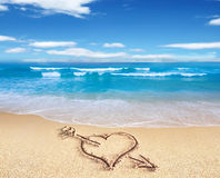 Heart with arrow, as love sign, drawn on the beach shore, with t Royalty Free Stock Photos