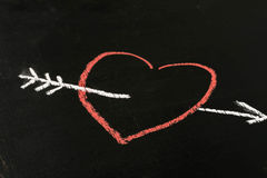 Heart and arrow chalk drawing on blackboard selective focus macro. Heart and arrow chalk drawing on blackboard background selective focus macro royalty free stock images