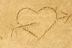 Heart and arrow drawing in sand. Background royalty free stock images
