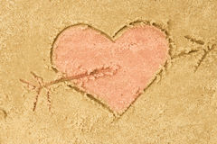 Heart and arrow drawing in sand. Background stock photos