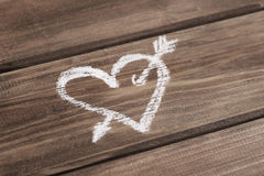 Heart with arrow drawn with chalk on wooden background Royalty Free Stock Photo