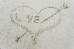 Heart with an arrow drawn on sand Stock Photography