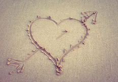 Heart with an arrow drawn on the sand Stock Images