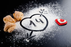 14. Heart with arrow on the flour on the black table. Cookies an Stock Image