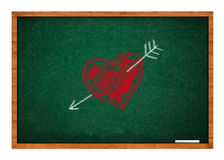 Heart and arrow on green chalkboard Stock Photos