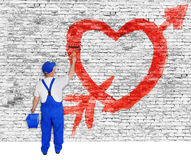 Heart and arrow painted on brick wall by man Stock Images