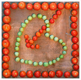 Heart with arrow symbol of love drawn with green and red tomatos. Heart with arrow symbol of love drawn with green and red tomatoes on wooden board, isolated on Stock Images