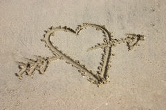 Heart with arrow written in sand. Heart written by hand in sand on the beach Stock Images