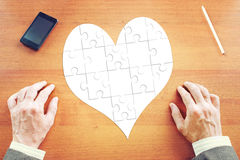 Heart as collected puzzles on the desk Royalty Free Stock Photos