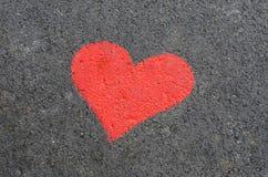 Heart on asphalt road Stock Photos